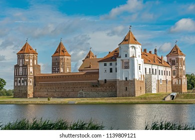Mir castle complex in the city of Mir in Belarus against a blue sky and a pond in the foreground.