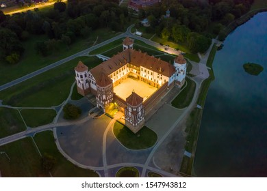 Mir Castle and its reflection in the lake in summer. Twilight and late evening. Aerial view from a drone.