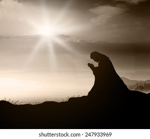 Miracle salvation concept: Silhouette Jesus Christ of Nazareth kneeling and praying at garden of gethsemane sunset background