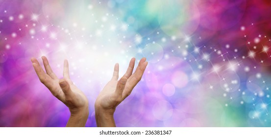 Miracle Worker - Outstretched open hands with magical sparkles on a pink and blue bokeh wide background