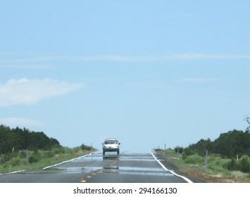 Mirage auf der Autobahn mit dem Auto an einem heißen Wüstentag im Juli in Arizona, Vereinigte Staaten.