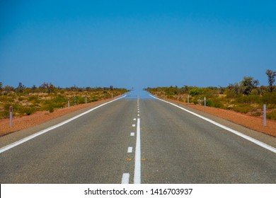 Mirage over straight endless road in Australia merging asphalt and sky