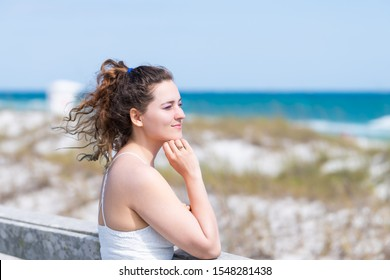 Miramar beach in Florida gulf of mexico panhandle ocean with closeup of one young happy woman girl in white dress leaning on wooden fence