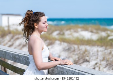 Miramar beach town village in Florida panhandle gulf of mexico ocean water with young happy woman girl in white dress leaning on wooden fence