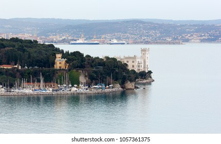 Miramare castle and the marina of Grignano in a winter late afternoon, with the seaport of Trieste, Italy, in the background