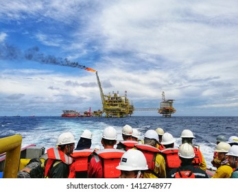 Miri, Malaysia - 8 May 2019 :Scenery back view a workers and consultant looking oil and gas platform performance with gas burning at Miri, Sarawak - Malaysiawith selective focus.
