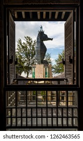 """Miri, Sarawak, Malaysia - December 5 2018: The iconic Seahorse Lighthouse at  the lifestyle and entertainment place """"Coco Cabana Miri"""", seen through a window with wooden blinds"""
