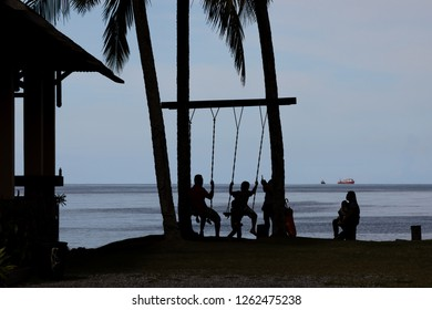 """Miri, Sarawak, Malaysia - December 5 2018: Silhouette of a family, using the swing at the palm beach of """"Coco Cabana Miri"""" - a Lifestyle and Entertainment Place"""
