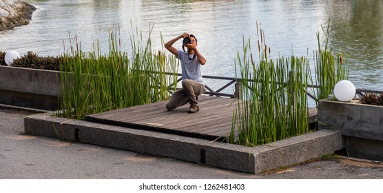 """Miri, Sarawak, Malaysia - December 5 2018: A male person with camera taking photos at """"Coco Cabana Miri"""" - A Lifestyle and Entertainment Place"""