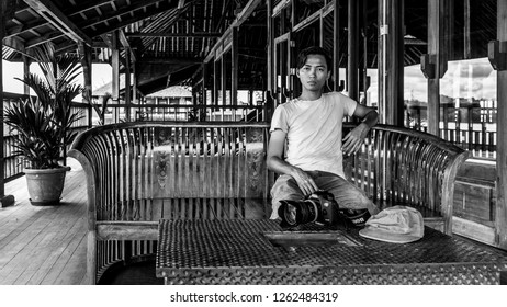 """Miri, Sarawak, Malaysia - December 5 2018: A male person with camera is sitting on a bench of the intricately carved wooden event hall at """"Coco Cabana Miri"""" - A Lifestyle and Entertainment Place"""