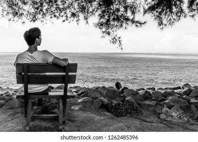 """Miri, Sarawak, Malaysia - December 5 2018: A male person is sitting on a small bench and is watching the sea at """"Coco Cabana Miri"""""""