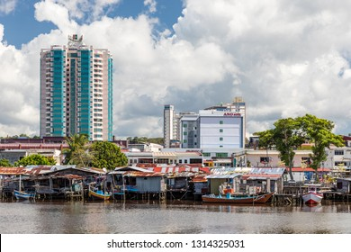 Miri, Sarawak, Malaysia - December 5 2018: Miri Waterfront with stilt houses and fisher boats, seen from the opposite site of Baong River at Pulau Melayu. Big building left: Imperial Hotel.