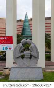 """Miri, Sarawak, Malaysia - December 5 2018: Sculpture of two people, reading books, in front of  """"Pustaka Miri"""", the public library of Miri."""
