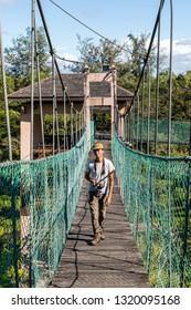 Miri, Sarawak, Malaysia - December 6 2018: A young man walking on the swing bridge in the Public Park Miri (malay: Taman Awam Miri)