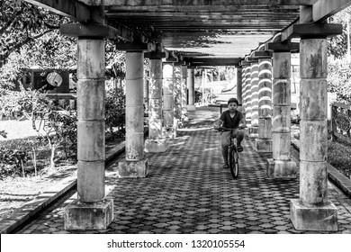 Miri, Sarawak, Malaysia - December 6 2018: A young boy is riding his bicycle at the portico of the Public Park Miri (malay: Taman Awam Miri)