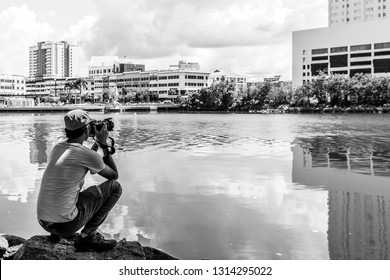 Miri, Sarawak, Malaysia - Decvember 5 2018: A photographer squatting at the border of Miri River to take a photo of Miri Waterfront