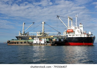 miri,malaysia december15 2017 : loading of logs is underway between 2 ships in the southern china sea.