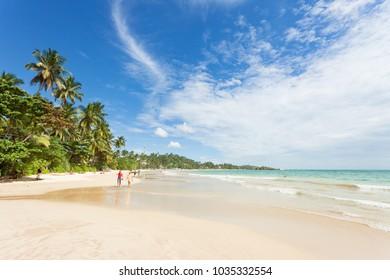 Mirissa Beach, Sri Lanka, Asia - DECEMBER 2015 - Tourists walking on the sand while enjoying the view across the wonderful beach of Mirissa