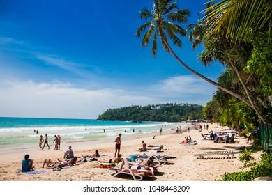 Mirissa Beach, Sri Lanka - JAN 2, 2017:  Tourists walking on the sand while enjoying the view across the wonderful beach of Mirissa on Jan 2, 2017. Sri Lanka.