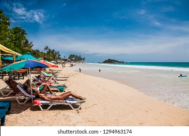 Mirissa Beach, Sri Lanka - JAN 2, 2017:  Tourists on the sand while enjoying the view across the wonderful beach of Mirissa on Jan 2, 2017. Sri Lanka.