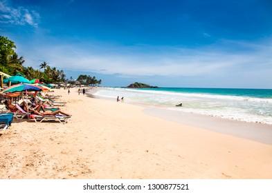 Mirissa Beach, Sri Lanka - JAN 2, 2017:  Tourists on the sand while enjoying the view across the wonderful beach of Mirissa on Jan 2, 2017. Sri Lanka.