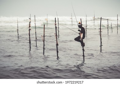 Mirissa, Sri Lanka - 07 26 2020: Traditional Stilt fishermen holding a fishing rod, and a bag for collecting fish, sitting on a stick cross above the seawater surface patiently waiting.