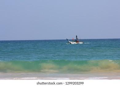 Mirissa, Sri Lanka - April 20, 2013: A local fishing boat with fishermen in it at the Mirissa Beach.