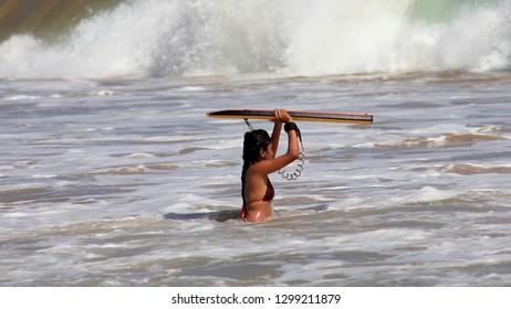 Mirissa, Sri Lanka - April 20, 2013: A young Asian girl tries her hands at surfing at the Mirissa Beach in Sri Lanka