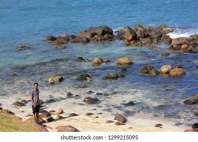 Mirissa, Sri Lanka - April 20, 2013: A young man stands at the beautiful Mirissa Beach and looks up!