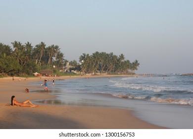 Mirissa, Sri Lanka - April 21, 2013: A girl in red bikini lies on the sand at the Mirissa Beach