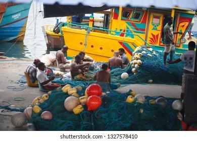 Mirissa, Sri Lanka - March, 25, 2018: Traditional Sri Lanka fishing boats in the Mirissa harbor. Fishermen unravel fishing nets.