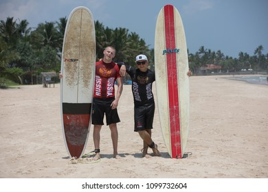 Mirissa/Sri Lanka - April 4, 2018: Two sports men stand on the beach with surfboards.