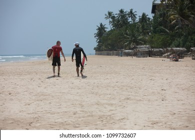 Mirissa/Sri Lanka - April 4, 2018: Two men dressed in rashguard walking along the beach with a surfboard.