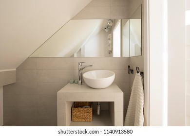 Mirror above washbasin in beige bathroom interior on attic with towel. Real photo