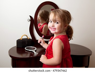 Mirror, Mirror.  Adorable preschooler in front of a mirror and putting on make up.