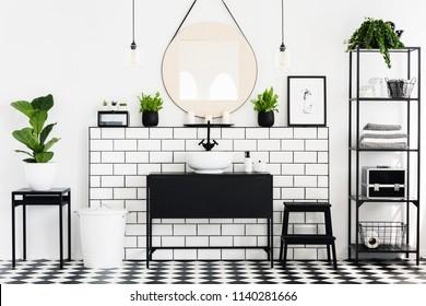 Mirror between plants above black washbasin in bathroom interior with checkered floor. Real photo