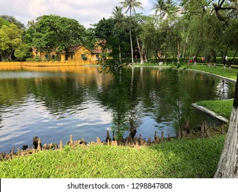 a mirror of the blue sky and green trees on the pond - Shutterstock ID 1298847808