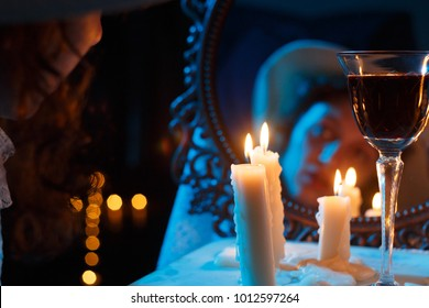 mirror with blurred female face candles and red wine