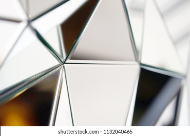 Mirror with crystals in wall, decoration and reflection. Abstract glass background. Polygonal surface. Close-up.