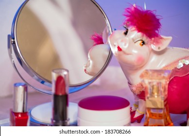 In the mirror desktop look pink piggy toy around her are all sorts of cosmetic things and lipstick red.
