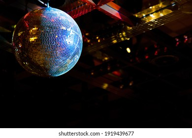 Mirror disco ball with light reflection hanging on ceiling in nightclub. Colorful glowing disco ball closeup on black background. Night party background with copy space for text