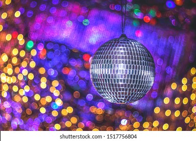 Mirror disco ball on beautiful shiny background with bokeh. Festive abstract image with defocused lights. Disco party. Copy space.