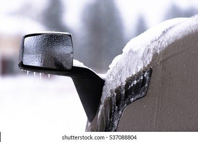 Mirror and fender of semi truck in snow and ice on blurred background