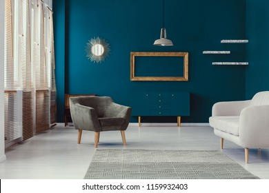 Mirror and gold frame with mockup in blue flat interior with armchair and grey settee. Real photo
