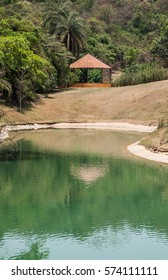 Mirror house reflected in green lake in Inhotim