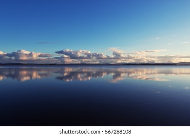 Mirror image of clouds on the horizon reflected in the calm waters of a deep blue lake in Oregon.