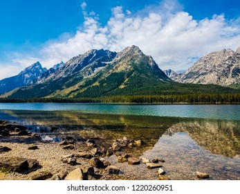 The mirror image reflections of the mountains, sky, and clouds upon Leigh Lake in the grand Teton National Park, are spectacular.The rocky shoreline makes a more interesting image in the foreground.