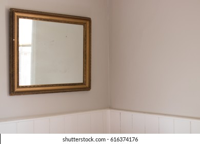 Mirror isolated on blank wall in country cottage with reflection of nearby window
