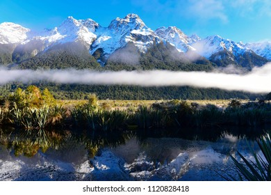 Mirror Lake and its perfect reflection of snow mountains in Fiordland National Park, New Zealand