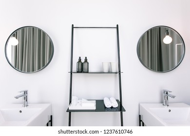 Mirror and lamp above two washbasins in B&W interior style